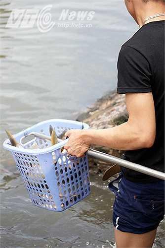 Chỉ chưa đầy 10 phút bắt cá trong miệng cống, chiếc rổ của người thanh niên này đã đầy cá.