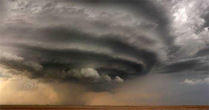 Lốc xoáy cuộn tròn với vận tốc gió cực lớn đang chuẩn bị quét qua. Người chạy theo cơn bão đã đứng ở cách đó không xa ghi lại những hình ảnh cận cảnh