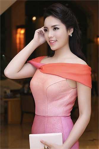 Chiếc ví gam hồng nhạt cầm tay có giá khoảng 12 triệu đồng được cô mix cùng váy hồng kiêu sa.