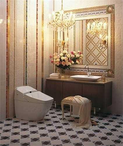 Buồng vệ sinh cũng được trang trí cầu kỳ với tông vàng, điểm xuyết đèn chùm tỏa ánh sáng vàng nhạt dễ chịu.