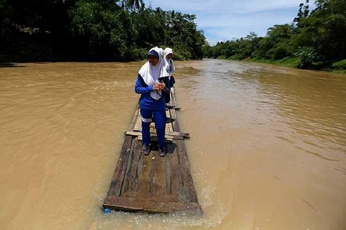 Trẻ em sống ở Cilangkap, Indonesia phải đến trường trên những 'chiếc thuyền' tạm bợ khi chiếc cầu duy nhất bắc qua sông Ciherang bị lũ cuốn trôi