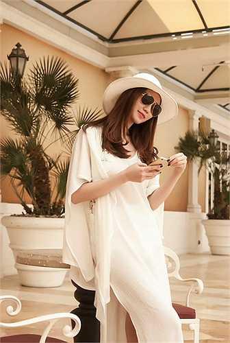 Khánh My chọn chiếc đầm trắng hở lưng gợi cảm đi cùng sandal thấp và túi Chanel cam bắt mắt