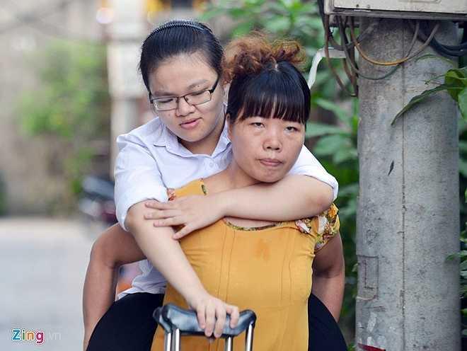 Chị Hà cõng con gái từ ngõ ra đường, sau đó hai mẹ con đi xe ôm đến trường thi. Cô gái sinh năm 1996 cho biết, ngồi trên lưng mẹ luôn có cảm giác yên tâm, ấm áp.