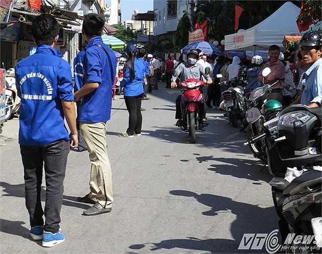 Trong khi đó, hàng loạt sinh viên tình nguyện (SVTN) đang căng mình 'dựng dải phân cách' để điều tiết giao thông trước cổng trường.