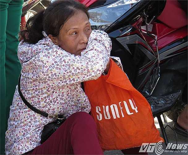 Nắng nóng, người mẹ mướt mồ hôi ngồi chờ sĩ tử  ngoài cổng trường thi.