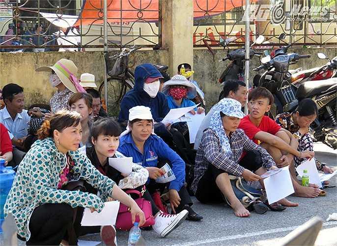 Phụ huynh đội nắng tám chuyện chờ các sĩ tử vào đăng ký dự thi tại cổng khu B - Trường Đại học Hàng hải Việt Nam.