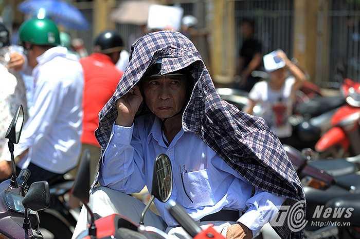 Không còn bóng mát, vị phụ huynh này phải dùng áo chống nắng khoác lên đầu.