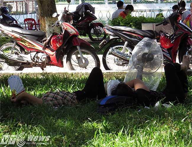 Hai bà mẹ ngả lưng giữa công viên chờ sĩ tử