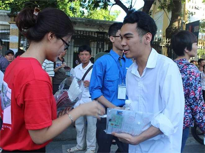 Nữ tình nguyện viên phát nước và bút miễn phí cho thí sinh.