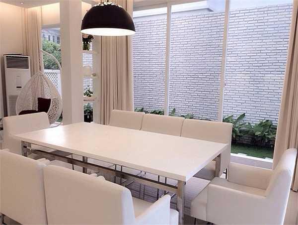 Khu bếp và bàn ăn nối liền phòng khách với các vật dụng trang trí đều có gam màu trắng sang trọng.