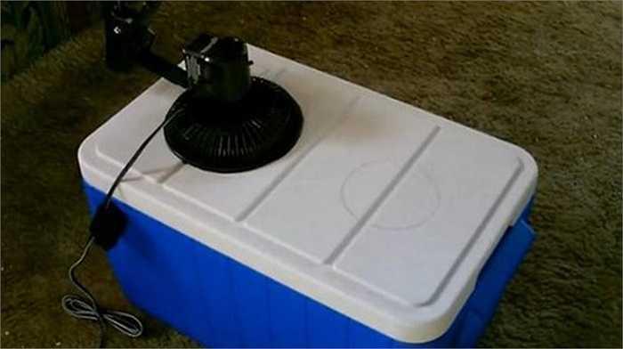 Đặt quạt vào vị trí đã đánh dấu (chú ý thân quạt vẫn ở 1/2 bên ngoài). Dùng keo dán cố định lồng quạt vào nắp thùng đã cắt.