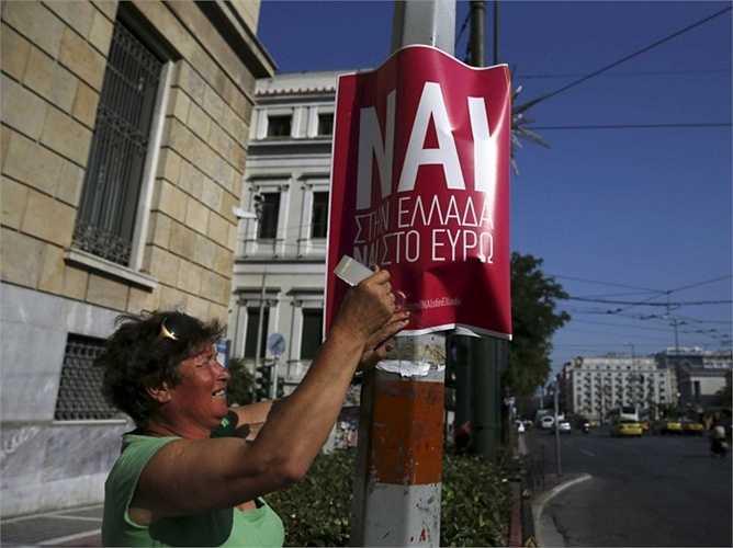 Một người phụ nữ đang cố gắng dán tấm biểu ngữ 'đồng tình với Hy Lạp, với đồng euro'.