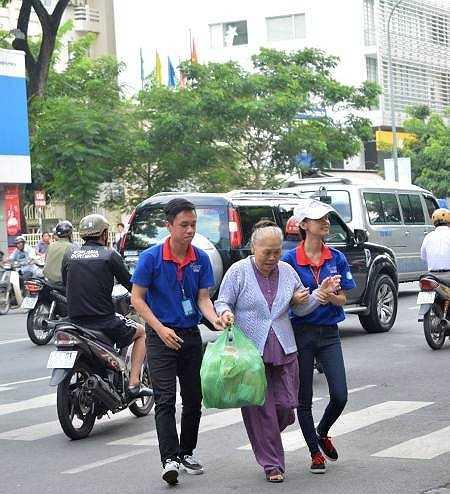 Tình nguyện viên dẫn một cụ già qua đường - Ảnh: Internet