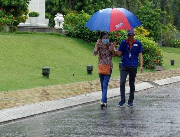 Tình nguyện viên đưa đón thí sinh đến phòng thi để tránh bị ướt mưa - Ảnh: Internet