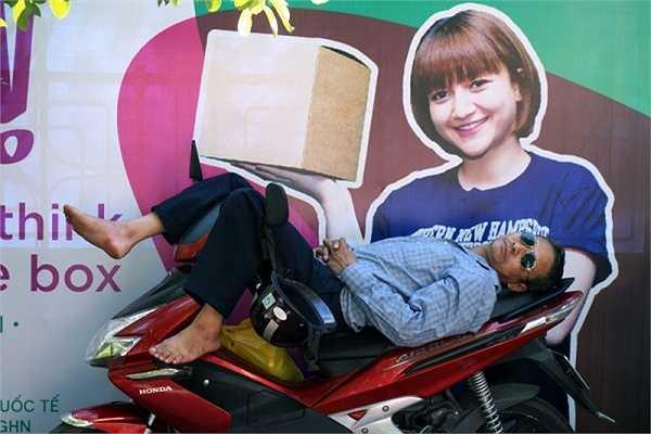Tranh thủ đợi con, phụ huynh ngủ một giấc say ngay trên xe máy. (Ảnh: Lê Anh Dũng/ Vietnamnet)