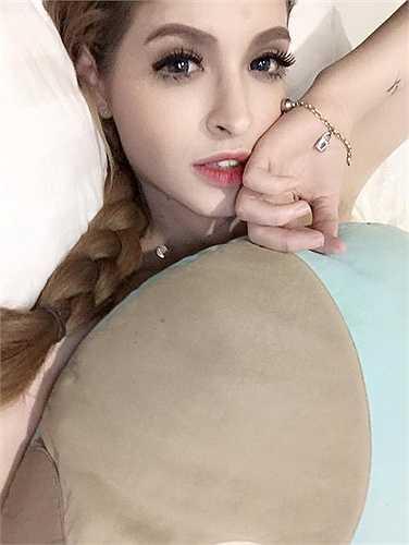 Người mẫu Andrea với gương mặt trang điểm kỹ trên giường. Cô thậm chí còn đeo kính áp tròng xanh.