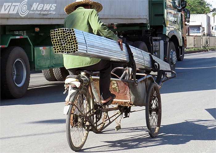 Bác xích lô ghồng mình chở cả tấn sắt thanh, với chiều dài 5-6m trên đường Nguyễn Văn Linh (quốc lộ 5)