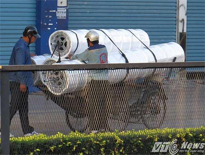 Một chiếc xích lô chở đến 4 cuộc cửa cuốn, chằng buộc qua loa, gây nguy hiểm cho người tham gia giao thông nếu gặp sự cố trên đường Nguyễn Văn Linh (quốc lộ 5).