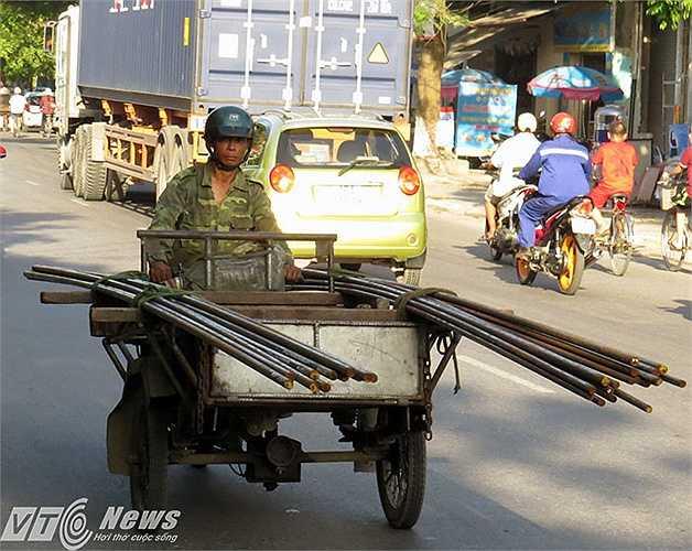 Xích lô máy chở sắt cây dài 5-6m lao vun vút trên đường.