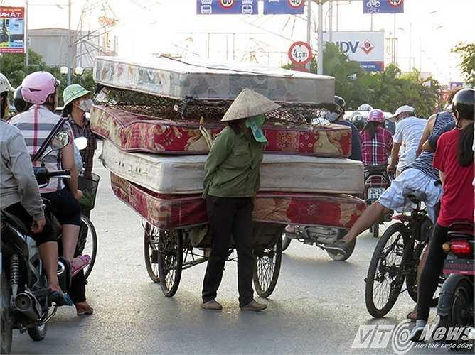 Một chiếc xích lô được chất lên 5 chiếc đệm cồng kềnh 'đối đầu' với người đi xe mô tô tại tại ngã tư đèn tín hiệu giao thông trên đường Lê Hồng Phong.