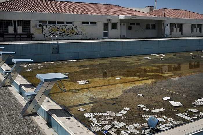 Bể bơi mọc rêu, chứa đầy rác.