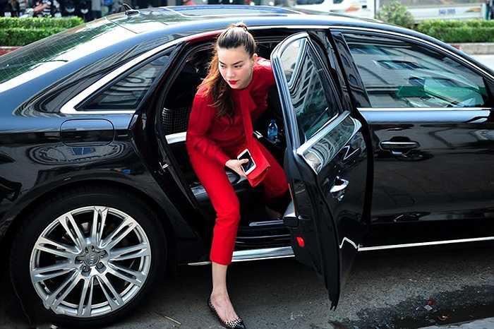 Hồ Ngọc Hà dùng bộ trang phục màu đỏ nổi bật bên cạnh chiếc xe hơi hạng sang màu đen.