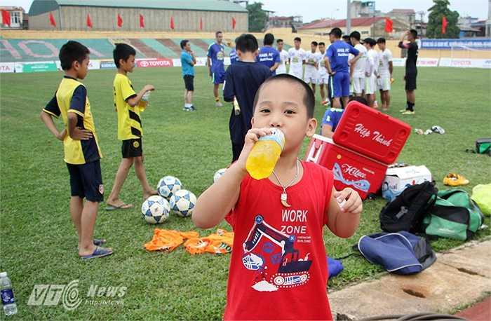 Một fan nhí chui hàng rào vào sân và được các cầu thủ tặng nước uống.