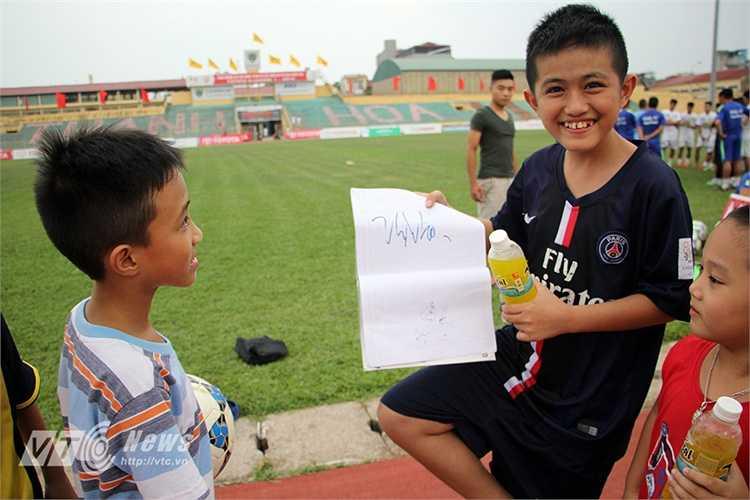 Anh Quang khoe thành quả của cả buổi là chữ ký của thần tượng Công Phượng. (Hà Thành)