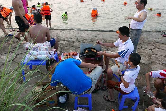 Người dân đổ ra sông tắm đông, một số hàng quán đã kịp mọc lên để tranh thủ kinh doanh.  (Nguồn: VnExpress)