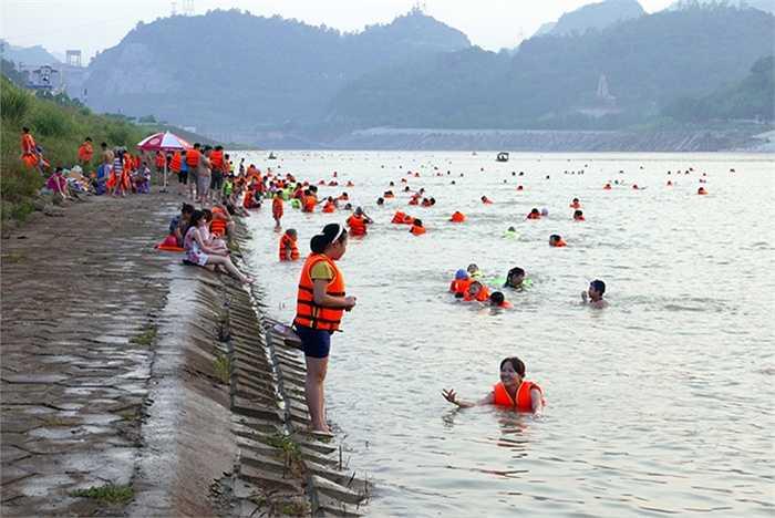Một đoạn bờ sông gần cầu Hòa Bình đông nghịt người tắm. Đây là bên hữu của sông Đà, nơi có bờ kè ngay ngắn chạy dọc sông khá thuận tiện cho người dân lên xuống nước.