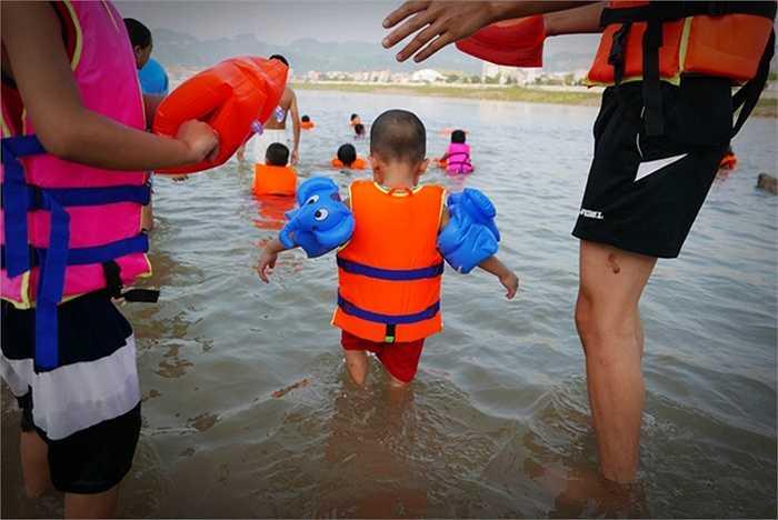 Nhiều em còn rất nhỏ cũng được gia đình đưa ra sông tập bơi.