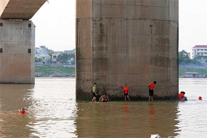 Nhiều thiếu niên bơi ra xa, trèo lên cả trụ cầu giữa dòng sông. Dù mặc áo phao, những chỗ như thế này vẫn rất nguy hiểm.