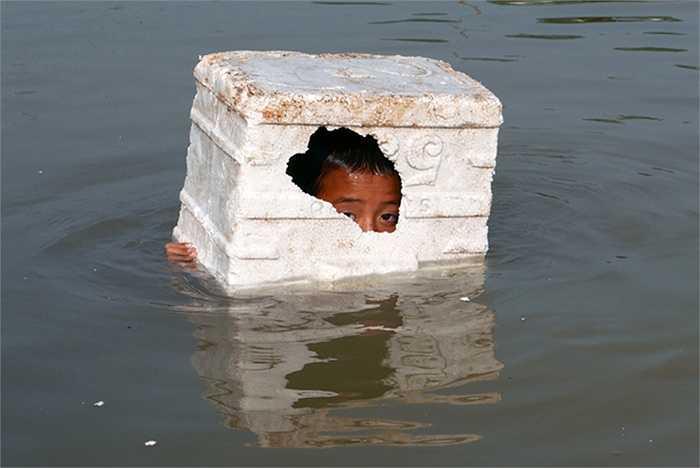 Một bé trai không có áo phao, dùng thùng xốp làm phao bơi.