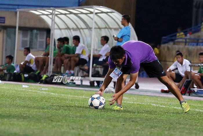 Một thành viên ban huấn luyện Hà Nội T&T tranh thủ chạy vào sân nhặt bóng khi không có trọng tài nào quan sát thấy có 2 trái bóng ở trên sân.(Ảnh: Phạm Thành)
