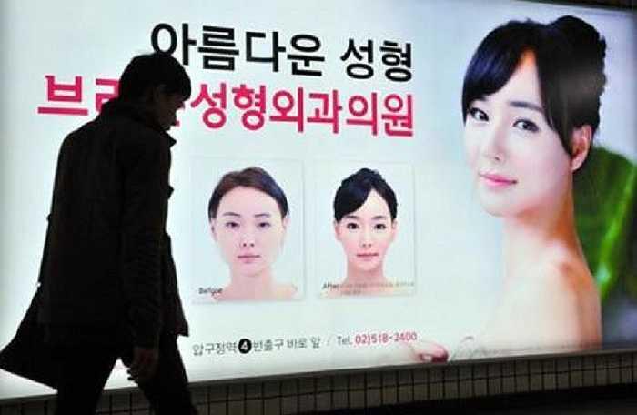 Một người đàn ông bước qua tấm biển quảng cáo khổ lớn về phẫu thuật thẩm mỹ tại một ga điện ngầm ở Seoul. Sau khi nhận được quá nhiều phàn nàn, quan chức thành phố đang tính chuyện hạn chế quảng cáo dạng này ở nơi công cộng.