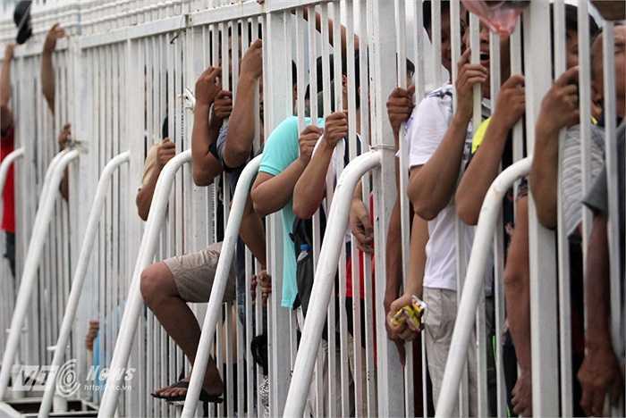 Quyết bám trụ, những cánh tay bám chặt vào hàng rào.
