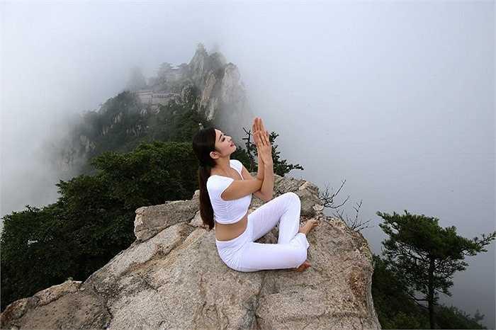 Trèo lên những vách đá cheo leo thế này để tập yoga là một kỳ công của người đẹp Trung Quốc