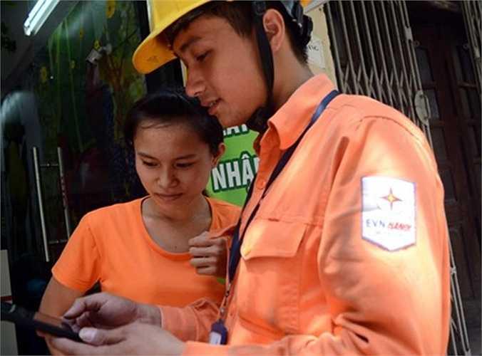Nhân viên Công ty Điện lực Cầu Giấy Hà Nội cho một khách hàng trên phố Trần Đăng Ninh xem hình ảnh ghi số điện sáng 9/7