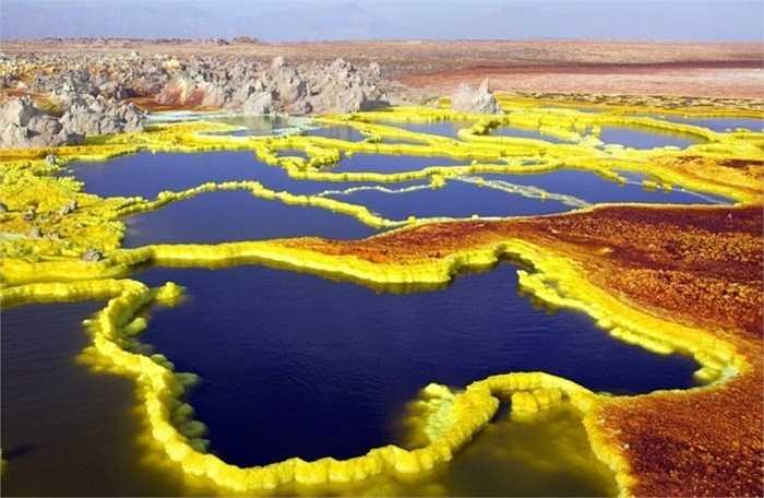 Dallol, Ethiopia. Khu vực ngay gần núi lửa đã ngừng hoạt động trong thời gian qua và là nơi sở hữu nhiệt độ khủng khiếp với mức trung bình hơn 41 độ C trong suốt gần 100 năm qua. Ngoài ra, Màu sắc tươi sáng và rực rỡ xuất hiện xung quanh khu vực miệng núi lửa như màu trắng, vàng, đất son, xanh lá cây và đỏ là do có sự kết hợp của những con suối nước nóng, núi lưu huỳnh, hồ axit, hồ oxit sắt, lớp muối ẩn. Không ngạc nhiên khi gần như không có người ở tại đây