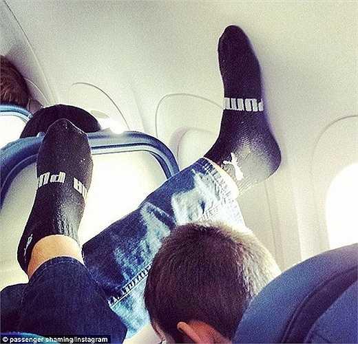 Một hành khách thoải mái ngủ ngon khi chân nguyên tất gác lên cửa sổ trước mặt một hành khách khác