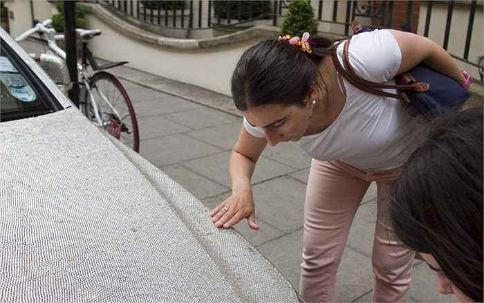 Người phụ nữ này đang chạm tay vào nắp ca pô nạm pha lê của một chiếc Mercedes Benz.