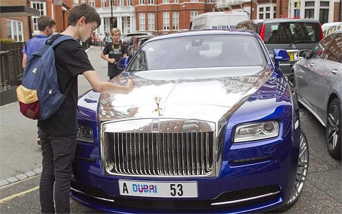 Một thiếu niên đang chụp hình chiếc Rolls Royce bóng loáng.