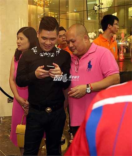 Quý tử nhà bầu Hiển thích thú với hình ảnh chụp cùng cầu thủ Man City. (Ảnh: Phạm Thành)