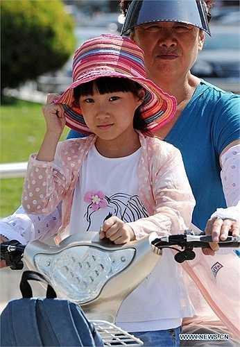 Cô bé trùm mũ cẩn thận khi ra đường vì nắng nóng