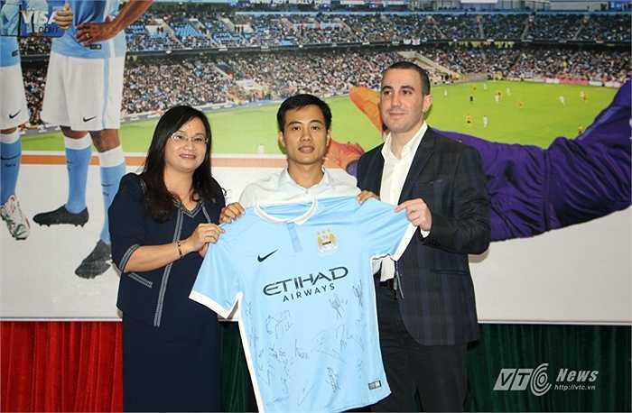 Đại diện Man City và nhà tài trợ SHB trao áo đấu kỷ niệm cho đại diện trường Đại học Ngoại ngữ Quốc gia Hà Nội.
