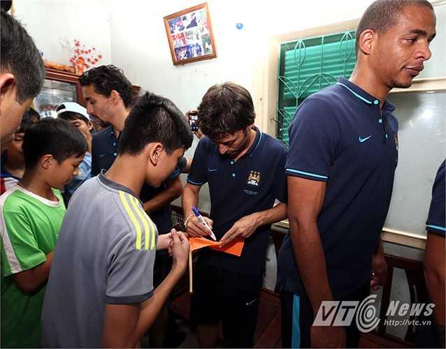 Anh ký tặng các bạn nhỏ hâm mộ Man City của làng trẻ SOS. (Ảnh: Quang Minh)