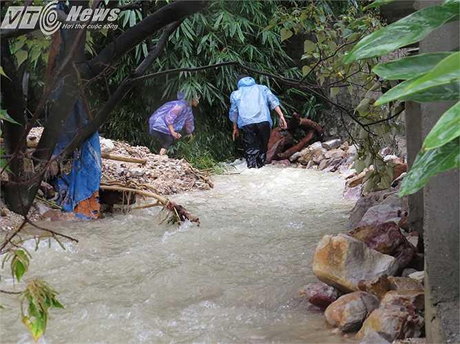 Chiều 27/7, nước mưa từ trên đồi vẫn dội xuống, người dân đang cố gắng bê đá kè tránh sạt lở tường nhà.