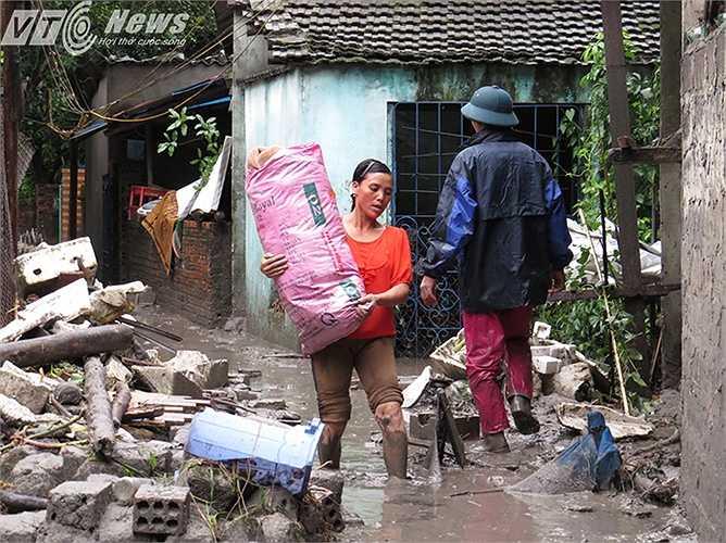 Bùn đất vẫn ngập khắp ngõ xóm, khiến việc di chuyển đồ đạc còn sót lại của người dân gặp nhiều khó khăn.