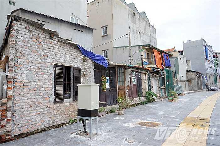 Một loạt những ngôi nhà được gia cố bằng tường gạch, tấm tôn, cửa gỗ méo mó, nhếch nhác.