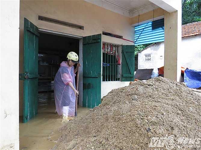 Gia đình bà Nguyễn Thị Minh, 53 tuổi, phía dưới hiện trường 3 ngôi nhà sập đổ, từ hôm qua vẫn thay nhau xúc cát đất từ lòng nhà, ngoài hiên do phía trên đổ xuống.